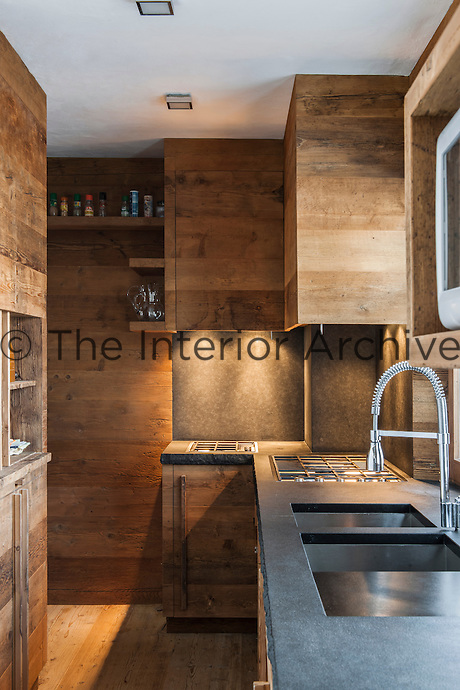 The contemporary wood-clad kitchen is complemented by a granite worktop, the edge left rough to break up the smooth lines