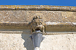 Gargoyle grotesque face drainpipe on medieval church wall Inglesham, Wiltshire, England, UK