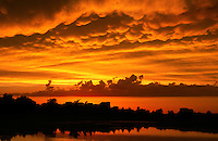 Mammatus clouds lit a vivid orange at sunset signal an end to a day of severe thunderstorms in Norman Oklahoma in June.