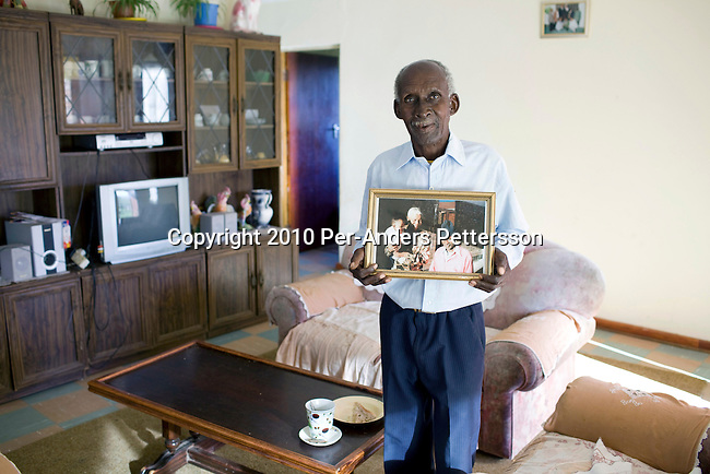 QUNU, SOUTH AFRICA - APRIL 1: Morson Mandela, age 78, stands with a portrait of himself and Nelson Mandela in his house in Qunu, where Nelson Mandela grew up on April 1, 2010, in Qunu, South Africa. Morson is the little brother of Mandela, (in the extended family) and he is the caretaker for the cemetery. Mr. Mandela was born in Mvezo, about 32 kilometers from here and Qunu and its surroundings is the area where he learned about life including his traditional manhood ceremony. Mr. Mandela was born in 1918, he served as a president of South Africa from 1994-1999, when he retired. Before that he was the leader of the armed wing of ANC and was convicted of sabotage among other crimes and served 27 years in prison, many of them on Robben Island, outside Cape Town. Qunu has a museum and Mr. Mandela has a big house where he and his family spends time while in the area. (Photo by Per-Anders Pettersson)