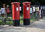 Two old traditional red pillar boxes in the street, Cambridge, England