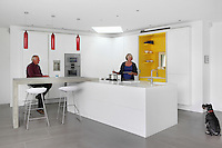 Caroline and Phillip Cooper and miniature schnauzer, Eric, in their modern kitchen designed by Chamber Furniture
