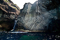 Waterfall running through the rocks of the coastline of Flores Island at the Azores
