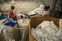 NWA Democrat-Gazette/ANTHONY REYES &bull; @NWATONYR<br /> Vivian Nichols, left, and Norma Perez, both with Northwest Rags, Inlc., cut torn pieces of rags apart Wednesday, Sept. 23, 2015 to salvage the rags at the company's facility in Springdale. Vance Brock, owner of Northwest Rags Inc., ships used clothing all over the world, and has a line of industrial rags, Ozark Recycled Wiping Rags.