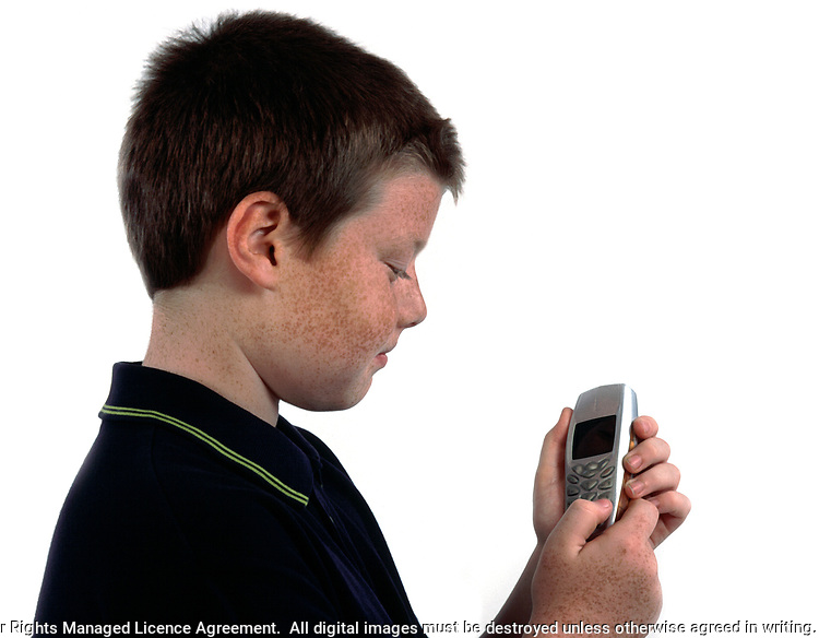 Mobile phone being used by a young boy. Model Release, age 10-11 years old