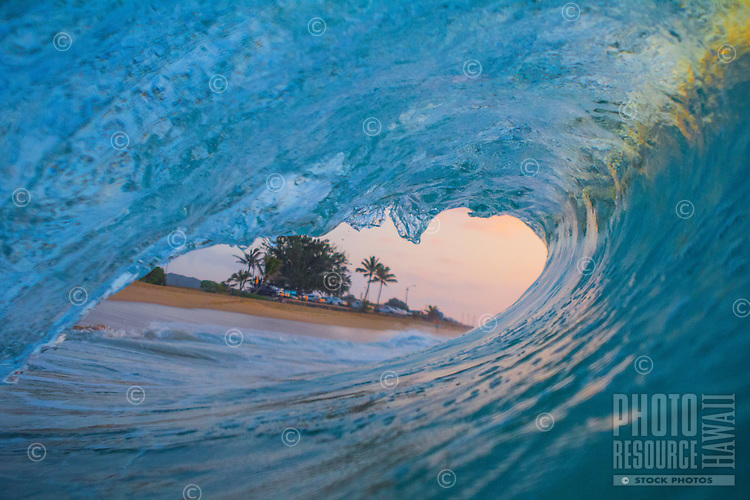 Sunrise colors come through a breaking wave at Sandy Beach, O'ahu.