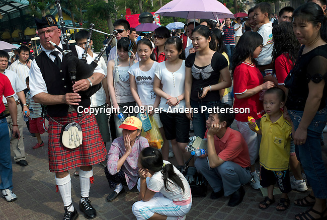 SHENZHEN, CHINA OCTOBER 1: A European bagpipe player performs for Chinese tourists at Interlaken Theme Park on October 1, 2008 outside Shenzhen, China. This copy of the Swiss alpine village of Interlaken has a 5-star hotel, a lake, Swiss streets, shops and entertainment. Its nestled in a mountainous area and also have a golf course and a forest train who takes visitors on a scenic tour. Chinese people love theme parks and new ones are opening constantly. It's estimated that there's about 2400 theme parks in the country. Many of the most popular parks are located around Shenzhen and over the border in Hong Kong. (Photo by Per-Anders Pettersson)....