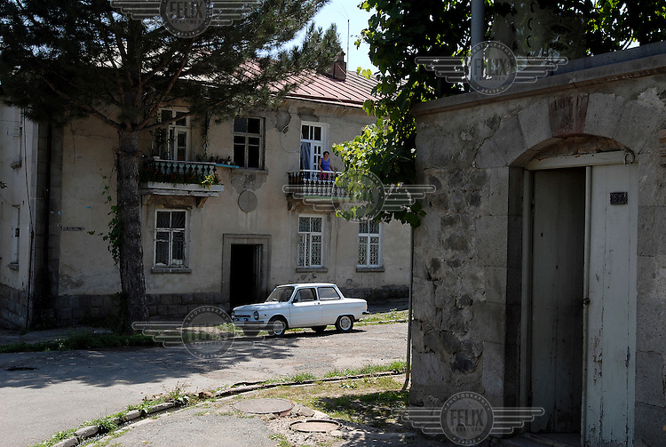 A woman stands on the balcony of her home in a sleepy corner of Goris.