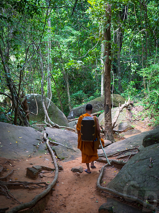 "A buddhist Monk returning from his pilgrimage to Kbal Spean (""Bridge Head"") is an Angkorian era archaeological site on the southwest slopes of the Kulen Hills to the northeast of Angkor in Siem Reap District, Siem Reap Province, Cambodia. It is situated along a 150m stretch of the Stung Kbal Spean River, 25 kilometres (16 mi) from the main Angkor group of monuments, which lie downstream."