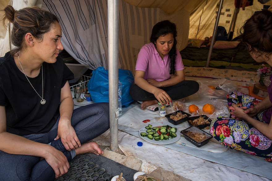 Sham Noh, 23, left, having lunch in her tent with two of her cousins. <br /> The Noh family, who are Yazidi, immigrated from Iraq due to the ISIS threat nearby. They are now stuck in Greece and living in Ritsona, a refugee camp outside of Athens. PHOTO BY JODI HILTON/PULITZER CENTER