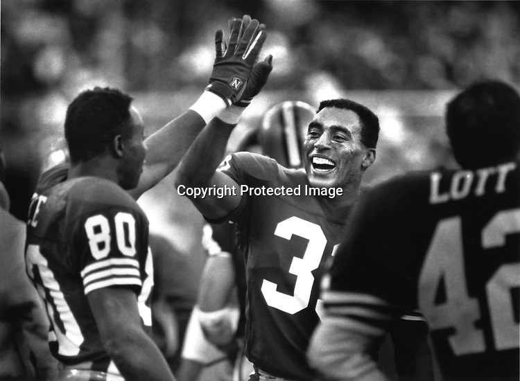 Jerry Rice and Roger Craig congratulate each other when it was apparent that they would defeat the Vikings 34-9 in a playoff win over Minnesota, at Candlestick Park, San Francisco, on Jan. 1, 1998.