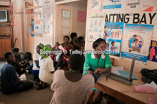 Pregnant woman has her blood pressure measured while other pregnant women sit on the floor waiting their turn to enter the consultation room in Arua Hospital, Uganda. Medical facilities are often overcrowded.