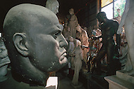 "April 27, 1990, Rome, Italy. Photographing for the book ""One day in the life of Italy"", an exploration of Rome. In Cinecitta, at the D'Angelis Sculpture warehouse, props such as the bust of Mussolini are stored. A man dusts statues."