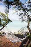 EXUMA, Bahamas. A hammock hanging on a tree outside one of the Villas at the Fowl Cay Resort.