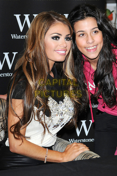 "Chloe Sims & fan.Signs copies of her new book ""The Only Way Is Up - My Story"" at Waterstones, Bluewater Shopping Centre, Greenhithe, Kent, England..18th November 2012.half length white black top sitting table signing pink .CAP/BRC.©Ben Rector/Capital Pictures."