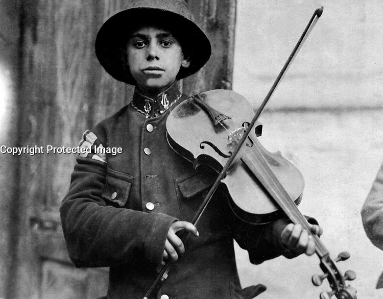 A Christmas street fiddler, Belgrade,  Serbia (Yugoslavia), December 1918.  American Red Cross. (War Dept.)<br /> Exact Date Shot Unknown<br /> NARA FILE #:  165-WW-489B-10<br /> WAR &amp; CONFLICT BOOK #:  676
