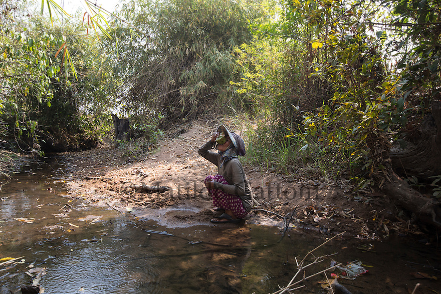 """Cambodia - Kampong Speu Province - Louv Veoun, 39, drinking fresh water from a nearby river. Before, when she had a land she used to have her own water well, now that she has lost everything she is forced to fetch water from unsafe rivers. """"I don't want money, I want my old land back. It is the land of my ancestors"""". Louv Veoun, 39 and mother of 8, was living in a small cottage on her rice field in Kork until March 2010, when she was dispossesed of her two hectares of land and compensated with 25 USD. She was forced to abandon her house and settle in a piece of land belonging to some of her relatives, close to the plantation. Today, she lives in utter poverty together with her family."""