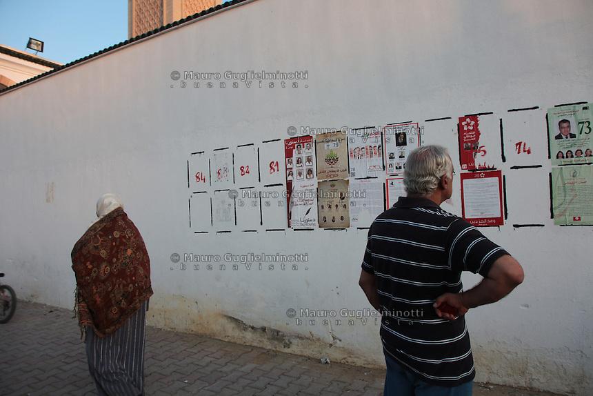 23 ottobre 2011 Tunisi, elezioni libere per l'Assemblea Costituente, le prime della Primavera araba: persone nei pressi del seggio elettorale. Sul muro sono appesi i manifesti elettorali dei vari partiti candidati. Un uomo li sta leggendo.<br /> premieres elections libres en Tunisie octobre <br /> tunisian elections