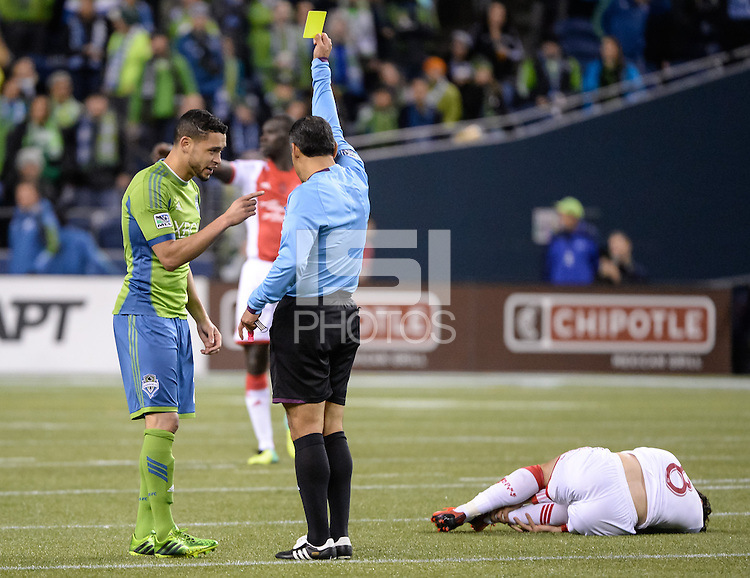 November, 2013: CenturyLink Field, Seattle, Washington: Seattle Sounders FC forward Will Bates (28) argues about a yellow card with referee Baldomero Toledo as Portland Timbers midfielder Diego Valeri (8) lays on the ground as the Portland Timbers take on the Seattle Sounders FC in the Major League Soccer Playoffs semifinals Round. Portland won the first match 2-1.