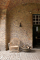 Resembling a painting by de Hooch an open door from the covered brick terrace leads to the shade of the kitchen beyond
