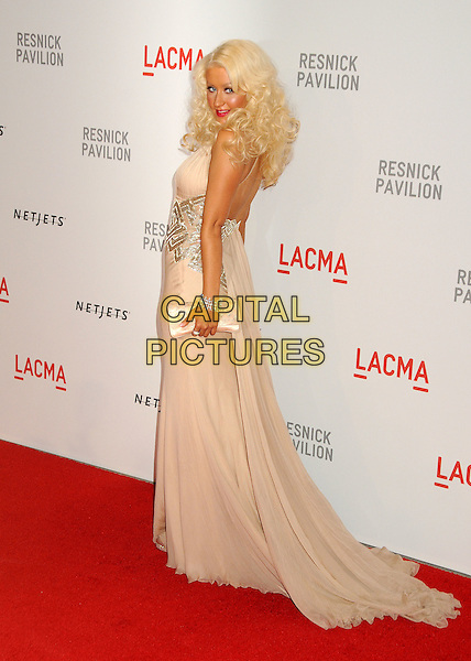 "CHRISTINA AGUILERA .at LACMA's ""The Unmasking"" The Lynda & Stewart Resnick Exhibition Pavilion Opening Gala at The Los Angeles County Museum of Art in Los Angeles, California, USA, September 25th 2010..full length long maxi dress gown train clutch bag  beige nude halterneck silk chiffon silver tattoo   bracelet     back rear behind side     .CAP/ADM/BP.©Byron Purvis/AdMedia/Capital Pictures."