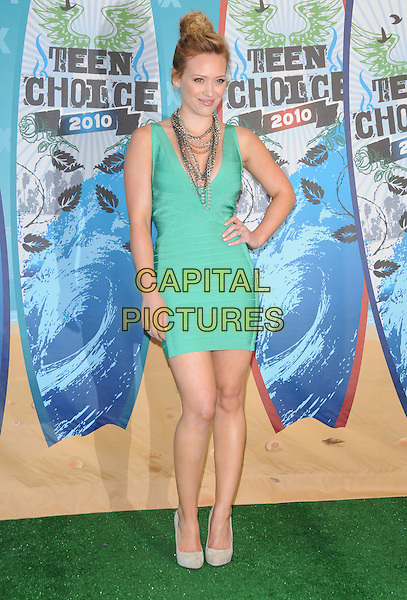HILARY DUFF .Fox Teen Choice 2010 Awards Press Room at the Universal Ampitheatre in Universal City, California, USA,.August 8th 2010.  .full length green dress herve leger bandage body con hand on hip beige suede shoes necklaces chains                                                                              .CAP/RKE/DVS.©DVS/RockinExposures/Capital Pictures.
