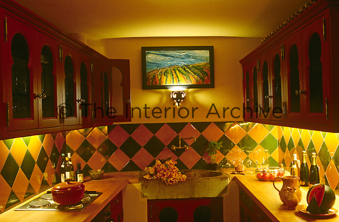 Yellow and green Provencale tiles are dramatically lit by recessed lighting under red-painted cupboards in this kitchen