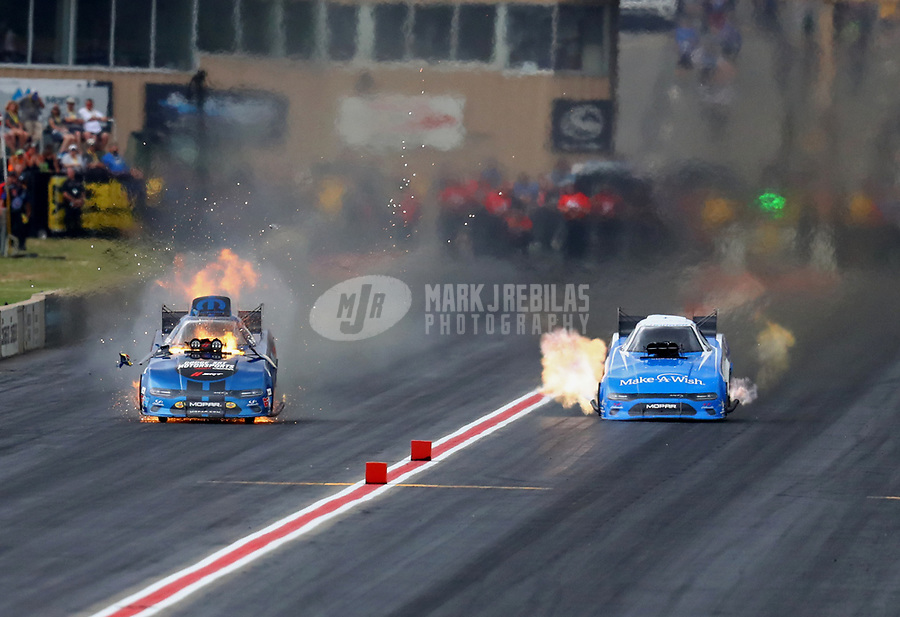 Jul 20, 2019; Morrison, CO, USA; NHRA funny car driver Matt Hagan (left) explodes an engine alongside Tommy Johnson Jr during qualifying for the Mile High Nationals at Bandimere Speedway. Mandatory Credit: Mark J. Rebilas-USA TODAY Sports