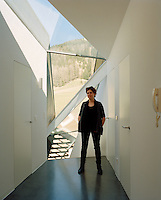 Architect Ulla Hell stands in the light-filled corridor of her modern chalet
