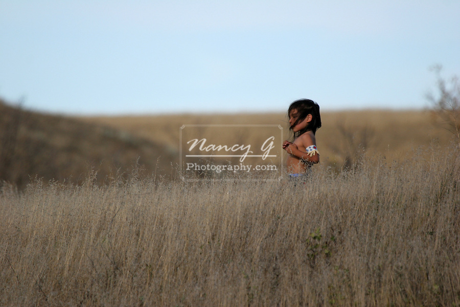 A Native American Indian boy standing in the dried grasses with the wind blowing his hair