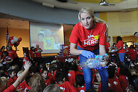 """NWA Democrat-Gazette/FLIP PUTTHOFF <br /> MARY MAE HERO<br /> Terianne Brown with Mrs. Fields brand cookies, distributes cupcakes to students at Mary Mae Jones Elementary in Bentonville during an assembly Friday Sept. 25 2015 honoring Mary Mae Jones, 91, as the winner of the """"Share Your Hero"""" contest sponsored by Mrs. Fields brand cookies of Broomfield, Colo. The contest drew nominations from around the world, a company representative said at the assembly.  Jamie Gaston, school nurse, nominated Jones for the award. Jones was chosen for her years of dedication to teaching and inspiring thousands of students.  Jones began teaching in Dumas in 1943 at age 19. She moved to Bentonville in 1962 and did not fully retire from teaching until 2005. Students at the assembly received cupcakes distributed by employees of Mrs. Fields brands. At right is Mike Poore, superintendent of the Bentonville district."""