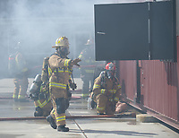 NWA Democrat-Gazette/ANDY SHUPE<br /> Mauro Campos (center), battalion chief for the Fayetteville Fire Department, closes a door Wednesday, March 7, 2018, as a training fire burns during a workshop for fire department leadership to meet current National Fire Protection Association standards at the Fayetteville Fire Department training facility in south Fayetteville. Thirty students and instructors from agencies in seven states attended the training meant to train department training officers at current standards.