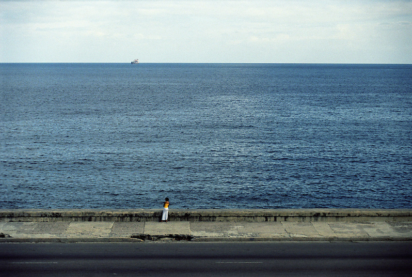 Two solitudes. A young Cuban woman looking out over Havana Harbor, a single ship on the horizon.