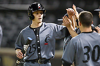 Will Drake (25) of the Cincinnati Bearcats high fives his teammates after scoring a run against the Wake Forest Demon Deacons at Wake Forest Baseball Park on February 21, 2014 in Winston-Salem, North Carolina.  The Bearcats defeated the Demon Deacons 5-0.  (Brian Westerholt/Four Seam Images)