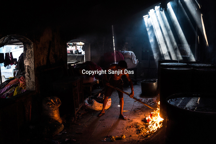 Sanjay, a dhobi (washerman) pushes small shreds of cloth to light it for boiling the cauldron of water and chemicals in Dhobighat in India's financial capital, Mumbai, India.