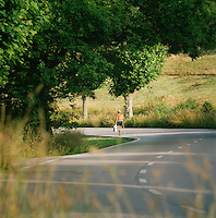 A man walking along the winding country roads outside Oviedo, Asturias, Spain