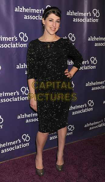 "Mayim Bialik.arriving at the 20th Anniversary Alzheimer's Association ""A Night At Sardi's"" at The Beverly Hilton Hotel in Beverly Hills, California, USA, .March 21st, 2012..full length black dress  hand on hip gold sparkly .CAP/ROT/TM.©TM/Roth Stock/Capital Pictures"