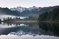 Dawn at Lake Matheson with reflections of Aoraki Mt. Cook (right) 3724m and Mt. Tasman (left) 3497m, two highest New Zealand mountains, Westland Tai Poutini National Park, West Coast, UNESCO World Heritage Area, New Zealand, NZ