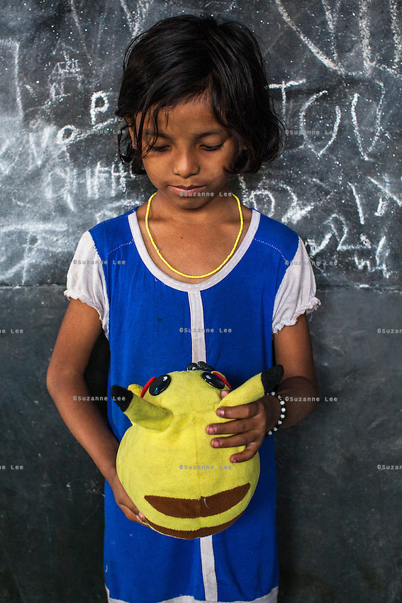 Krishna, 4, poses for a portrait with a soft toy in the Guria Non-Formal Education center in the middle of the Shivdaspur red light district, Varanasi, Uttar Pradesh, India on 20 November 2013. Guria uses the soft toys as a form of therapy for the children of the women in prostitution and also use it as signals of the children's emotional wellbeing.