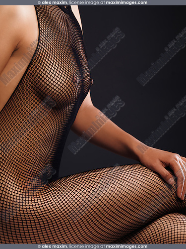 Closeup of a woman body in a sheer fishnet bodystocking