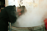 An Ultra-Orthodox Jew rinses kitchenware in steaming, boiling water to make it kosher in preparation for the upcoming Pesach (Passover) holiday, March 26,2002 in Jerusalem. In this pre-festival ritual, practicing Jews remove all traces of leavened products from their homes in observance of Passover, which recounts the hasty exodus of the ancient Israelites from Egypt. The eight-day holiday begins on Wednesday night. Photo by Quique Kierszenbaum