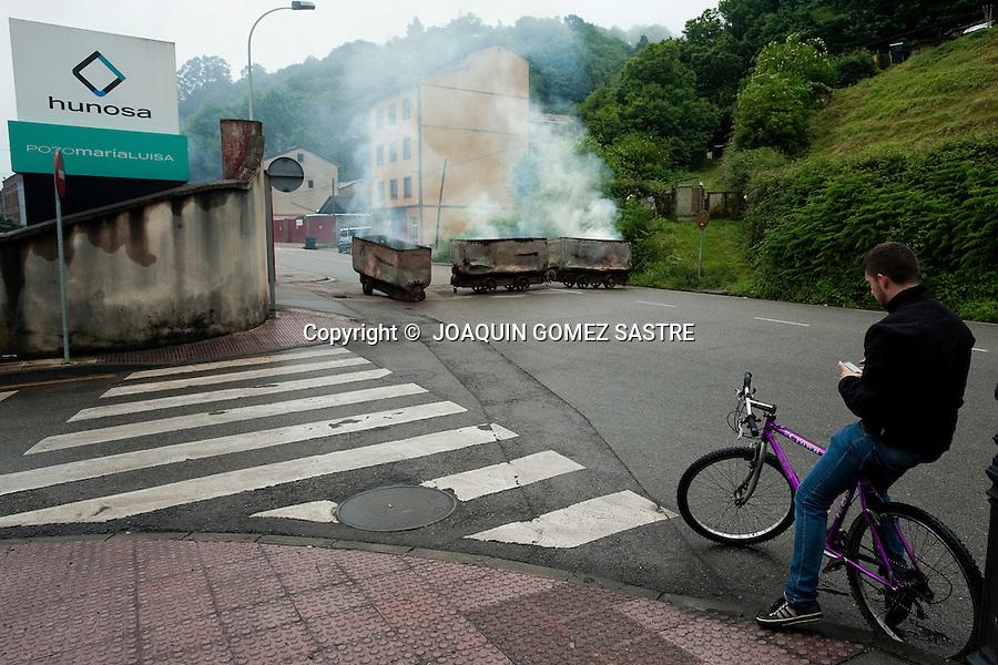 18 JUNIO 2012 LANGREO ASTURIAS .Un joven observa unas carretillas ardiendo que cortan una carretera por la huelga de los mineros alado del pozo maria luisa.foto © JOAQUIN GOMEZ SASTRE