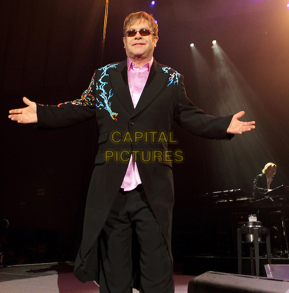 SIR ELTON JOHN.Sir Elton John performs at the 1st Mariner Arena in Baltimore, Md., USA..March 26th, 2011 .stage concert live gig performance music half 3/4 length black suit hands arms sunglasses shades pink shirt yellow blue print.CAP/RKE/EML.©EML/RockinExposures/Capital Pictures.