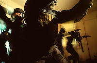 A police SWAT team with guns drawn and Kevlar body armor and helmet make entry into a house.