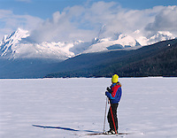 Skiers admiring snowy winter landscape on frozen Lake McDonald,GLACIER NATIONAL PARK, Montana