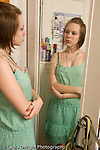 Teenage girl 15 years old at home in room looking at self in mirror