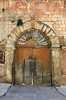 These massive doors of the Italian walled city Matera have been cut to include two smaller doors.