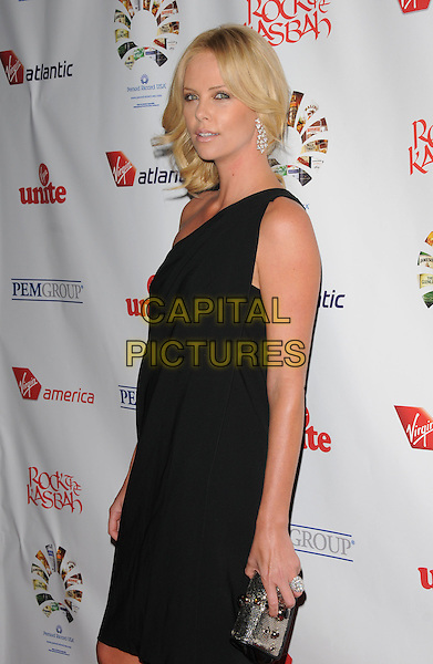 CHARLIZE THERON.The Virgin Unite Rock the Kasbah held at The Roosevelt Hotel in Hollywood, California, USA. .October 23rd, 2008                    .half length dress clutch bag silver black one shoulder                         .CAP/DVS.©Debbie VanStory/Capital Pictures.