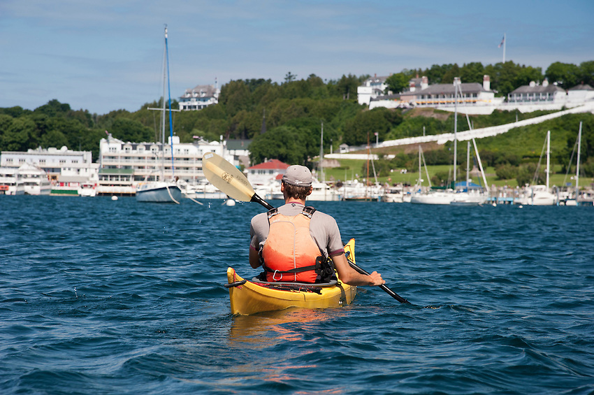 A kayaker enters the busy harbor and marina of Mackinac Island Michigan on Lake Huron.