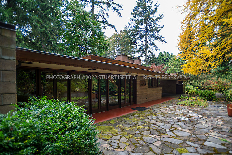 "10/9/2012--Sammamish, WA, USA..VIEW: Exterior showing main entrance (left) and car port (back, right)...Architect Frank Lloyd Wright planned his ""Usonian"" homes to be affordable for middle-class families. The 1,9500 square foot Brandes home is for sale in Sammamish, Washington (30 minutes from Seattle) at $1.39 million. It features three bedrooms, two bathrooms and a small, separate office/study space...The home was built in 1952, and has redwood trim and Wright's original furniture and some garden sculptures by Wright. It's one of only three Frank Lloyd Wright homes near Seattle...©2012 Stuart Isett. All rights reserved."